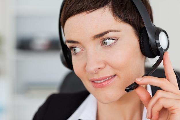 Sluit omhoog van een professionele secretaresse die met een hoofdtelefoon roept