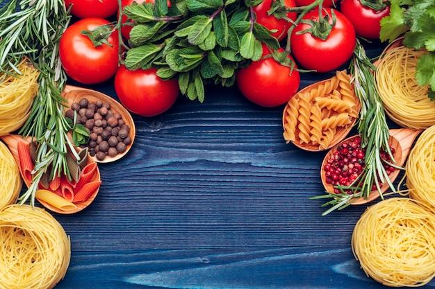 Sluit omhoog van een ruwe droge italiaanse deegwarenfettuccine op blauwe houten achtergrond