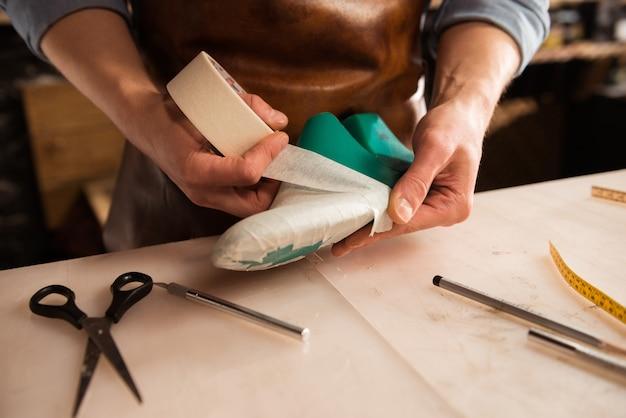 Sluit omhoog van een schoenmaker de schoen van modelleringsmensen