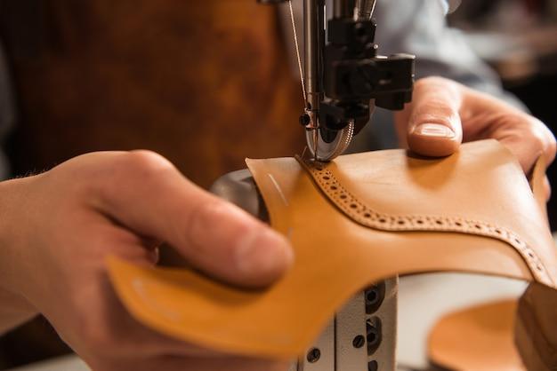 Sluit omhoog van een schoenmaker die een deel van schoen naait