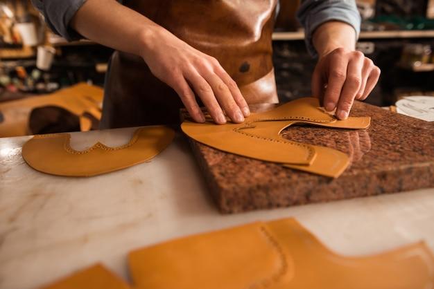 Sluit omhoog van een schoenmaker die leer meet