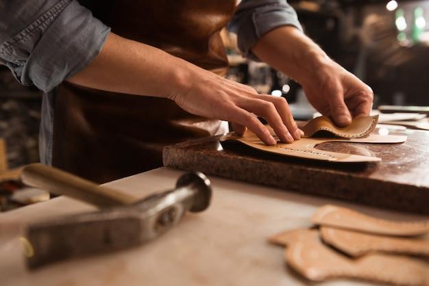 Sluit omhoog van een schoenmaker die met leer werkt