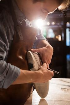 Sluit omhoog van een schoenmaker die metingen voor een schoen doet