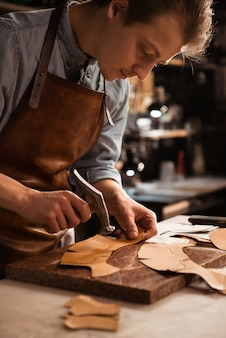 Sluit omhoog van een schoenmakersmens die met leer werkt