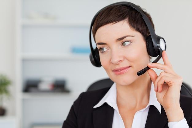 Sluit omhoog van een secretaresse die met een hoofdtelefoon roept