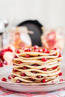 Sluit omhoog van een stapel van pannekoeken met granaatappelzaden op een plaat