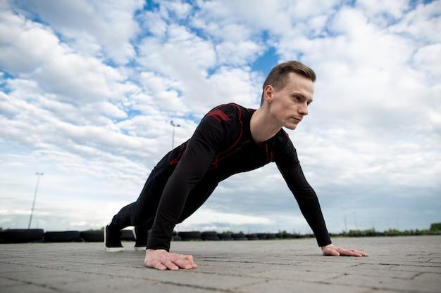Sluit omhoog van een sterke jonge mensenopdrukoefening op het asfalt van het sportterrein. man training in de ochtend. gezonde levensstijl, sport concept. kopieer ruimte