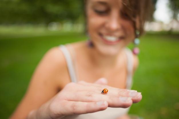 Sluit omhoog van een vage vrouw die zacht een lieveheersbeestje houdt