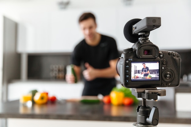 Sluit omhoog van een videocamera die jonge glimlachende mannelijke blogger filmen