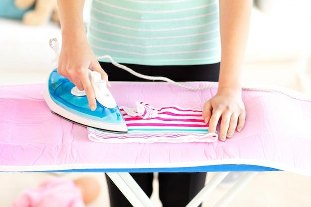 Sluit omhoog van een vrouw die haar kleren strijkt