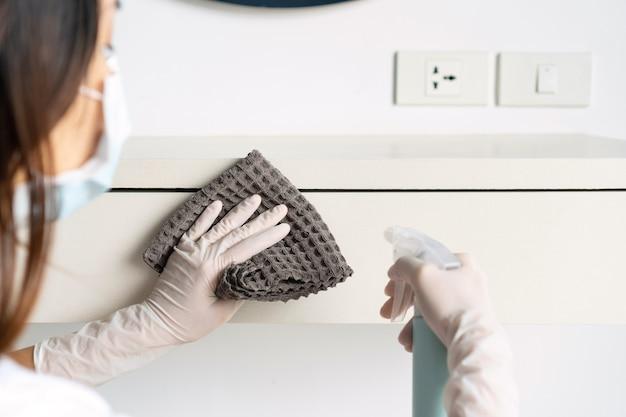 Sluit omhoog van een vrouw die masker en handschoenen draagt die een oppervlakte desinfecteren