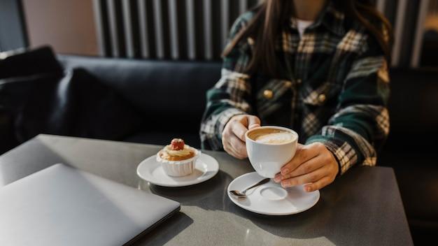 Sluit omhoog van een vrouw die van een koffiepauze geniet