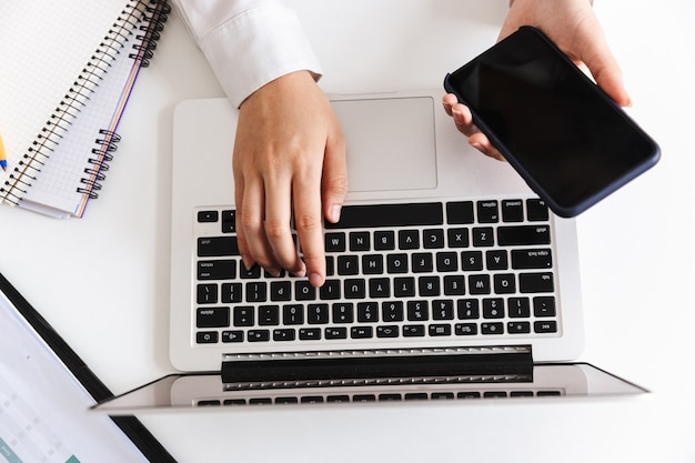 Sluit omhoog van een vrouw in wit overhemd typend op laptop computer