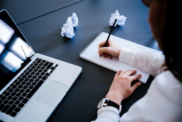 Sluit omhoog van een vrouwenhand schrijvend een contract met laptop naast thuis