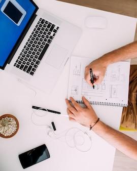 Sluit omhoog van een webontwerper die bij bureau werkt, op kladblok schetst