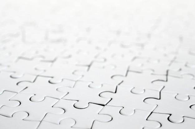 Sluit omhoog van een witte puzzel in geassembleerde staat in perspectief. vele componenten van een groot geheel mozaïek zijn verenigd