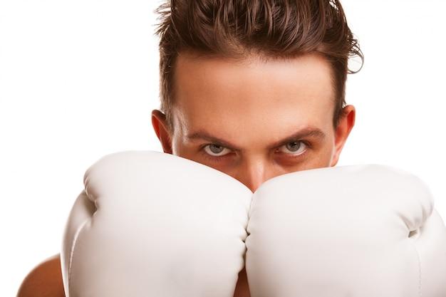 Sluit omhoog van een woeste mannelijke bokser die zijn vuisten in bokshandschoenen steunen