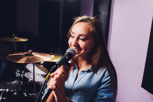 Sluit omhoog van een zanger die een spoor in een studio opneemt.
