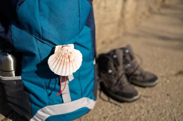 Sluit omhoog van een zeeschelpsymbool van camino de santiago op rugzak en trekkingslaarzen