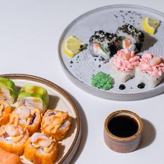 Sluit omhoog van eetstokjes die deel van sushibroodje nemen. sushi set rolt in lichte keramische plaat