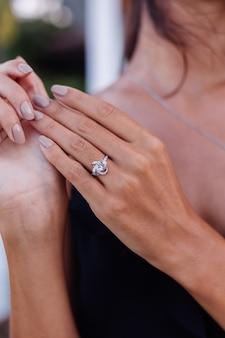 Sluit omhoog van elegante diamantring op vrouwenvinger. vrouw draagt zwarte jurk. liefde en huwelijk concept. zacht natuurlijk daglicht en selectieve aandacht.