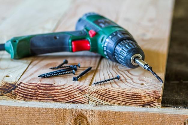 Sluit omhoog van elektrische schroevedraaier met sommige schroeven leggend op oude ruwe houten lijst of uitstekende natuurlijke planken. bouwen, repareren en huisonderhoud concept