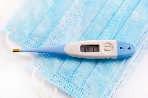 Sluit omhoog van elektronische thermometer en medisch masker wijzend op hoge koorts