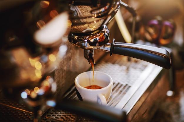 Sluit omhoog van espressomachine met kop.