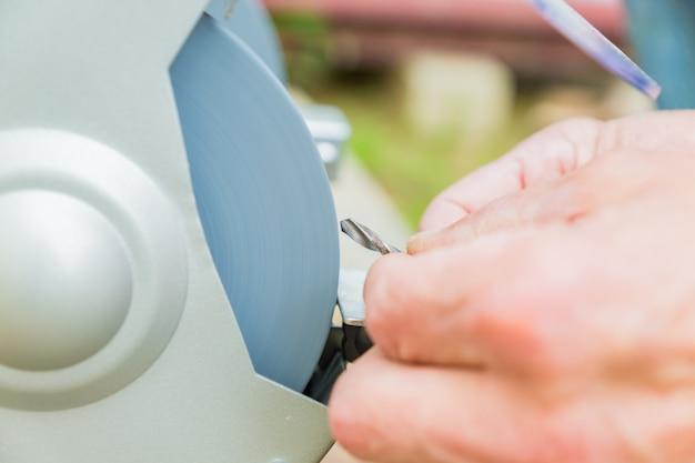 Sluit omhoog van fabrieksarbeider scherpende boor met de snijdersmachine van de slijpsteen schurende schijf