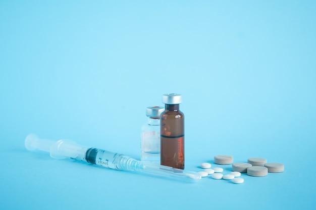 Sluit omhoog van flesje van geneeskunde en vaccin met spuit en tablet op blauw