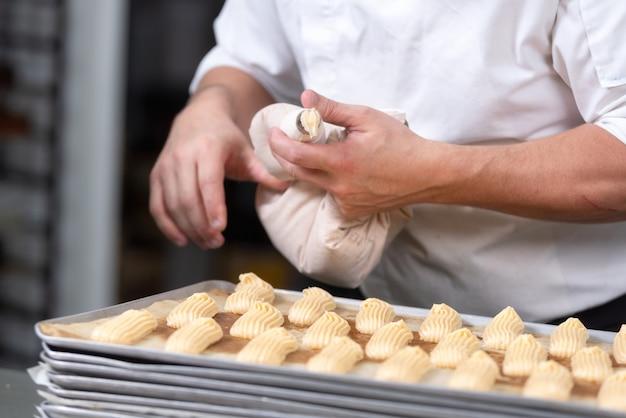 Sluit omhoog van gebakjechef-kok met banketbakkerszak die room drukken bij banketbakkerij.