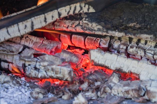 Sluit omhoog van gebrande houtskool in metaalfornuis