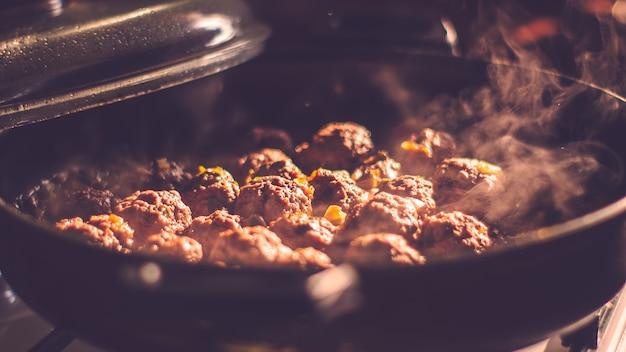 Sluit omhoog van gehaktballetjes die worden gekookt