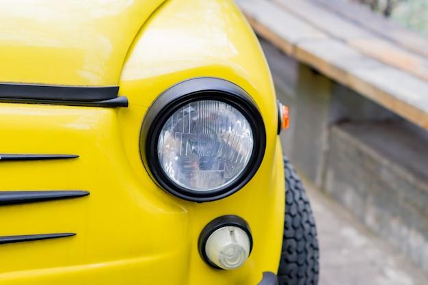 Sluit omhoog van gele retro auto met ronde koplampen.