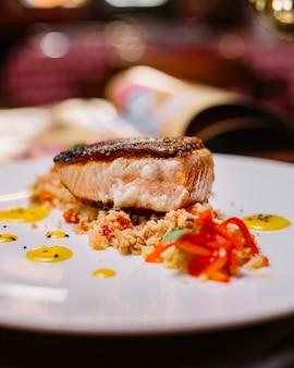 Sluit omhoog van geroosterd visfilet dat bovenop de kouskoussalade wordt gediend met groene paprika's