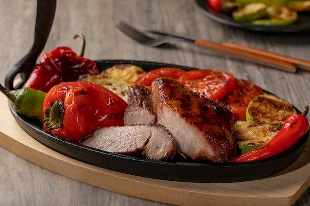 Sluit omhoog van geroosterd vlees op gietijzerpan met geroosterde groenten op rustieke houten lijst.