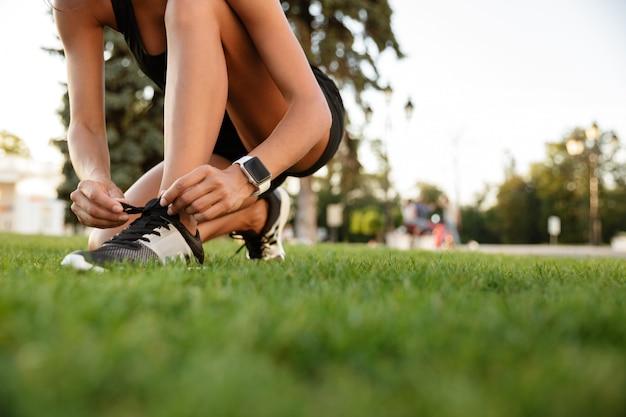 Sluit omhoog van geschiktheidsvrouw die haar schoenveters bindt