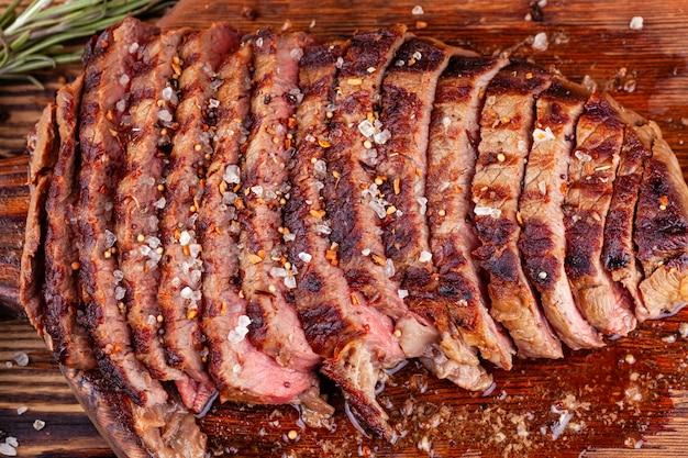 Sluit omhoog van gesneden geroosterd rundvleeslapje vlees met kruiden op houten scherpe raad