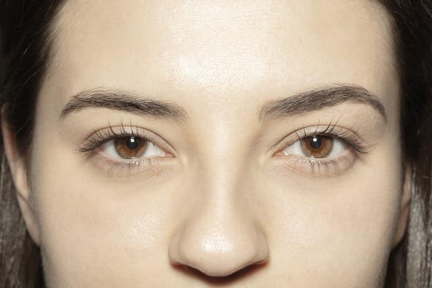 Sluit omhoog van gezicht van mooie kaukasische jonge vrouw, concentreer me op ogen