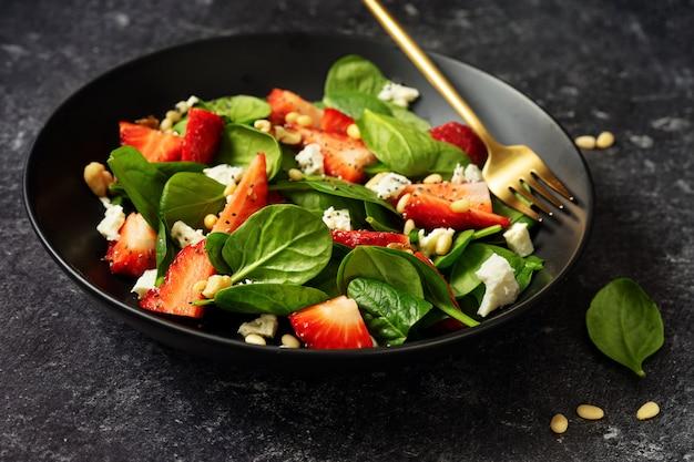 Sluit omhoog van gezonde aardbeisalade met spinazie, feta en pijnboompitten