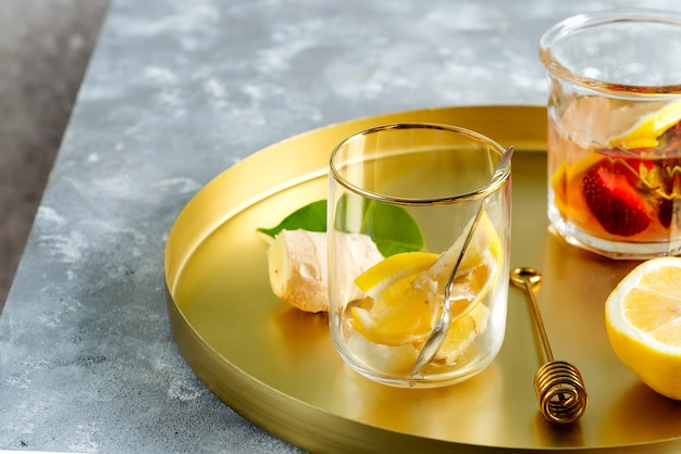 Sluit omhoog van gezonde ingrediënten voor gember, citroen en honingthee op een koperen dienblad