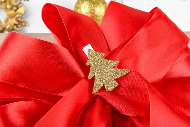 Sluit omhoog van gift met rode lintboog met gouden kerstboom op wasknijper op een wit