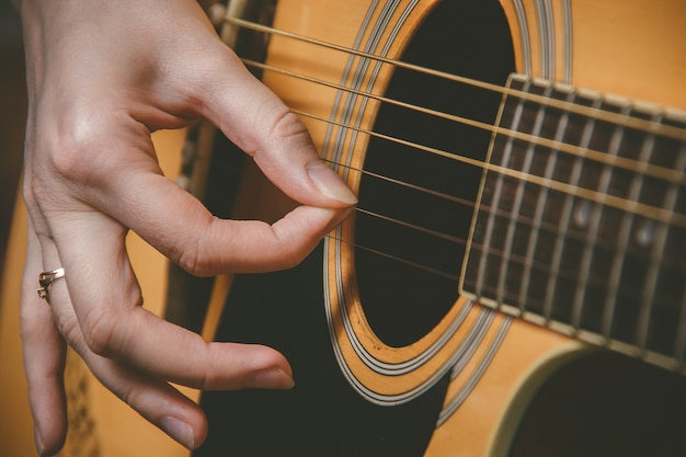 Sluit omhoog van gitaristhand het spelen gitaar