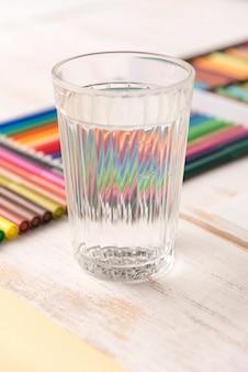 Sluit omhoog van glas met water dat zich dichtbij kleurrijke tellers bevindt