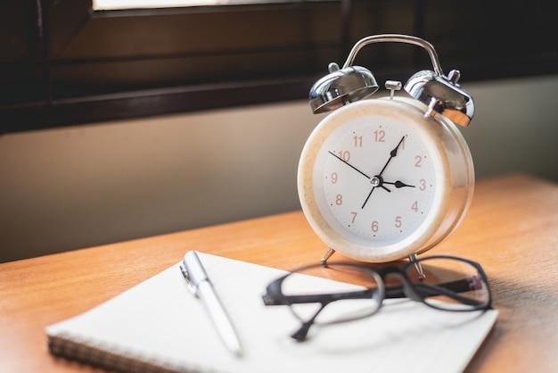 Sluit omhoog van glazen, klok en notitieboekje op bureaulijst