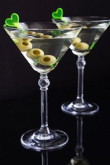 Sluit omhoog van glazen met martini en groene olijven