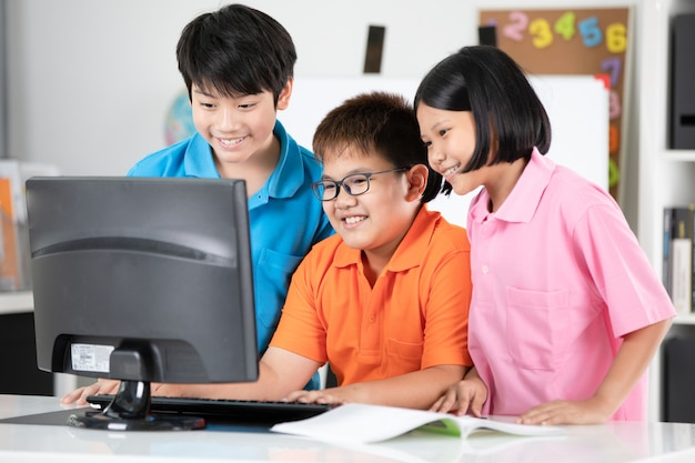 Sluit omhoog van glimlachende aziatische leerlingen gebruikend een bureaucomputer.