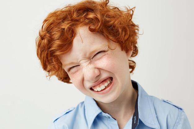 Sluit omhoog van grappige rode haired jongen die met sproeten glimlachend met gesloten ogen, dwaze gezichten maken