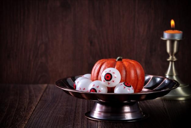 Sluit omhoog van griezelige halloween-trucs, concept het decor van het horrorfestival, pompoenlantaarn met kandelaar en rook.