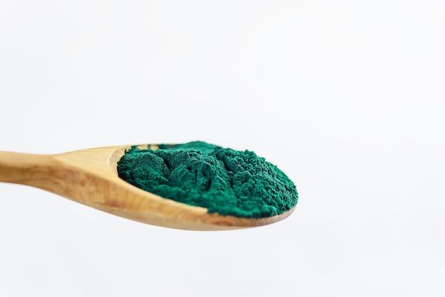 Sluit omhoog van groen spirulinapoeder in een houten lepel